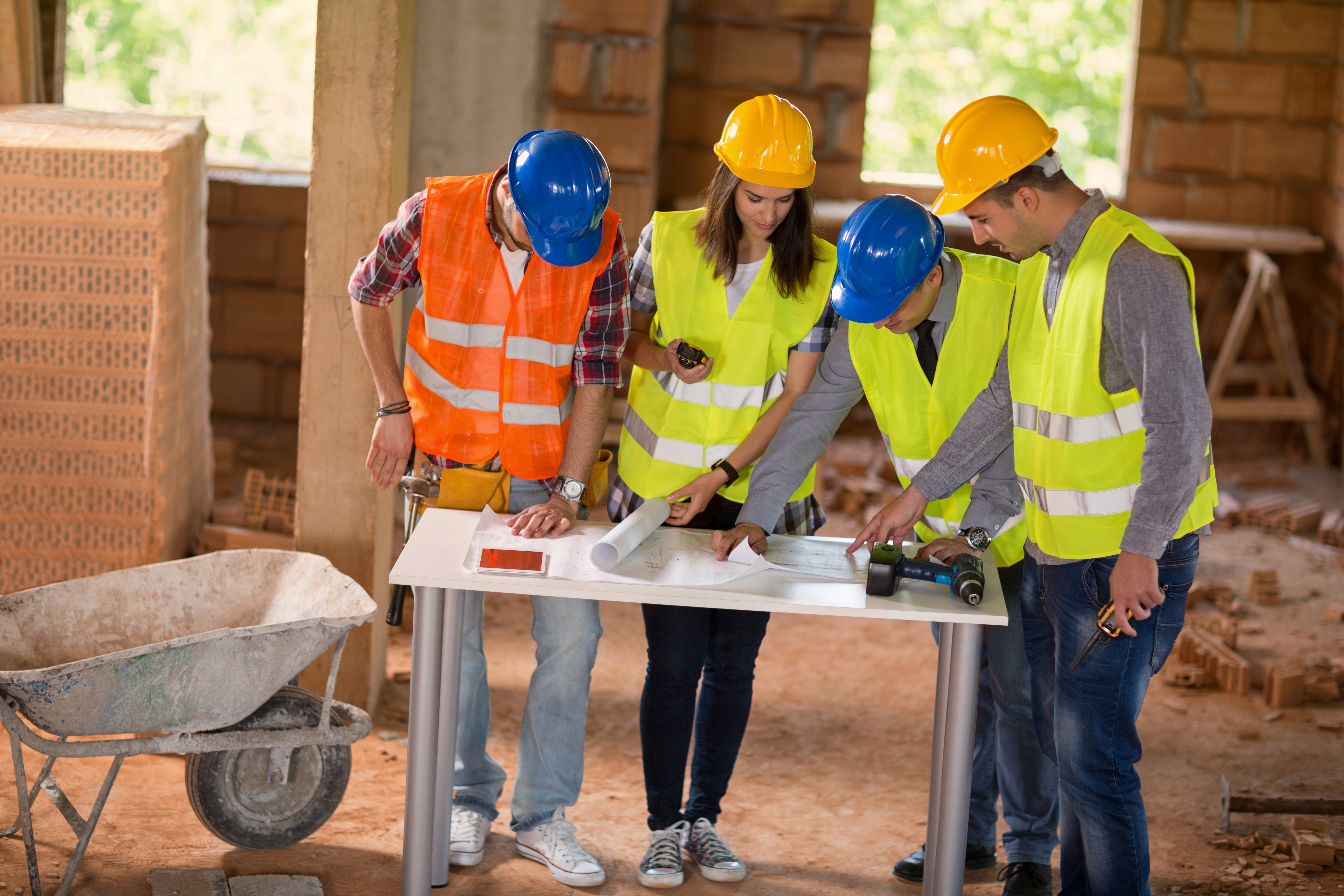 Experienced architect explain details of construction plan to colleagues at building site