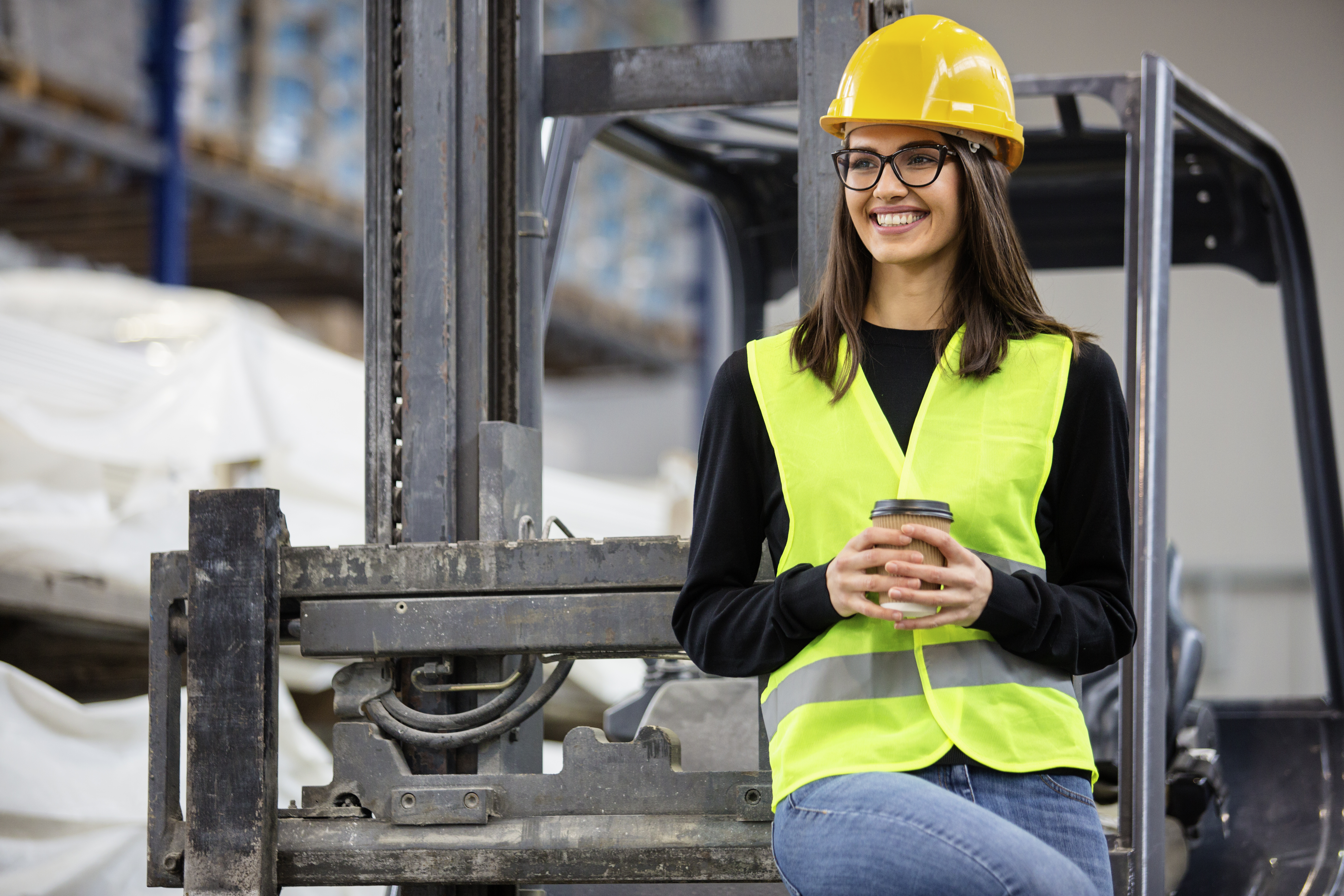 Girl at factory in a vest and helmet near forklift with coffee